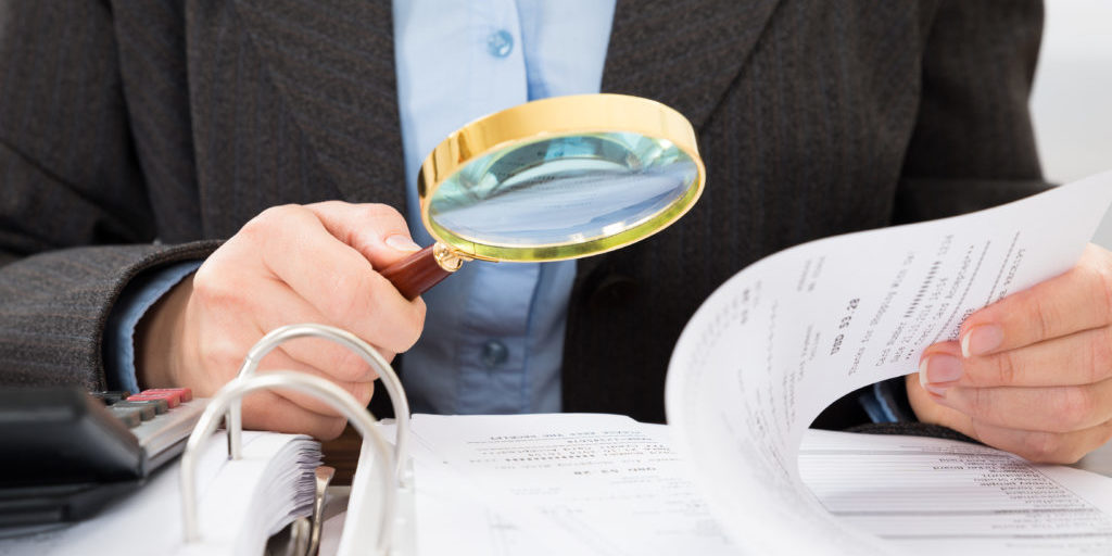 Close-up,Of,Businessperson,Checking,Bills,With,Magnifying,Glass